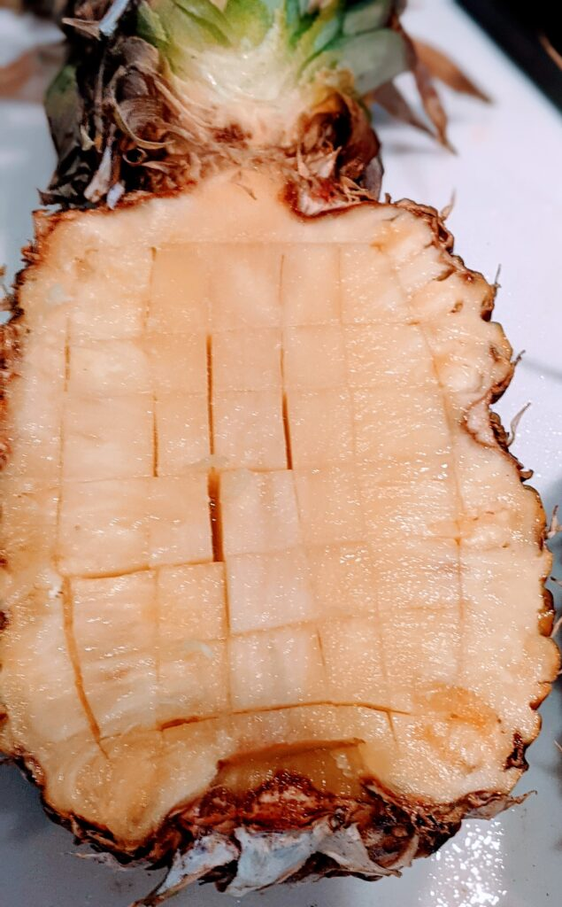 Showing how to cut pineapple to be hollowed.