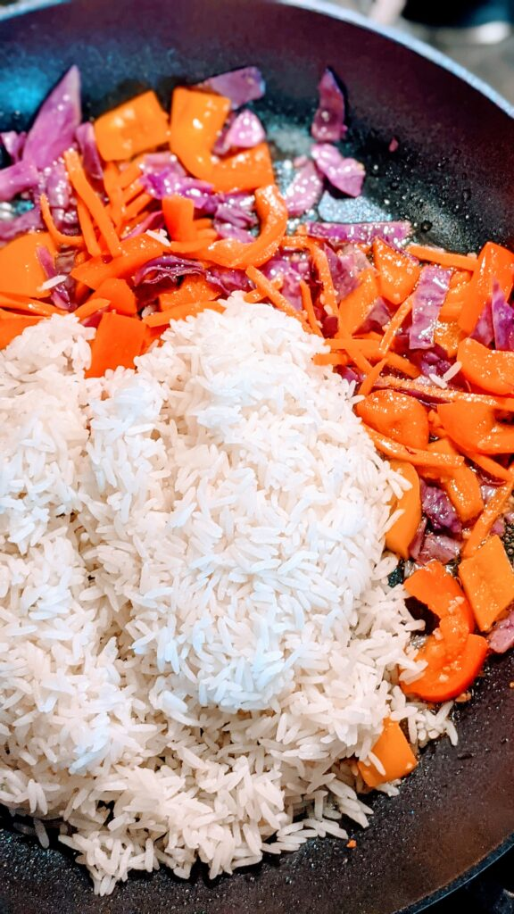 White rice with sautéed peppers, carrots and cabbage in skillet.