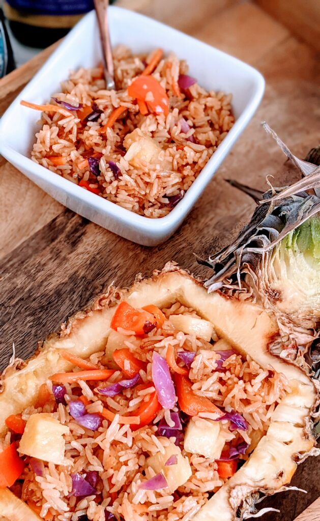 Easy Pineapple Fried Rice on a wooden serving board with a side of rice in a small square serving bowl.