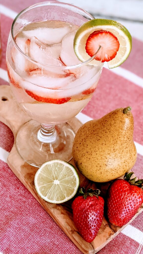 Goblet glass filled with Absolut Strawberry Pear.  Pear, half slice of lime and 2 strawberries all placed on tiny cutting board.