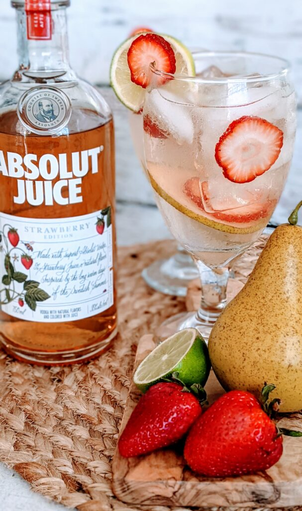 Cocktail with bottle of Absolut Juice and fruit alongside.