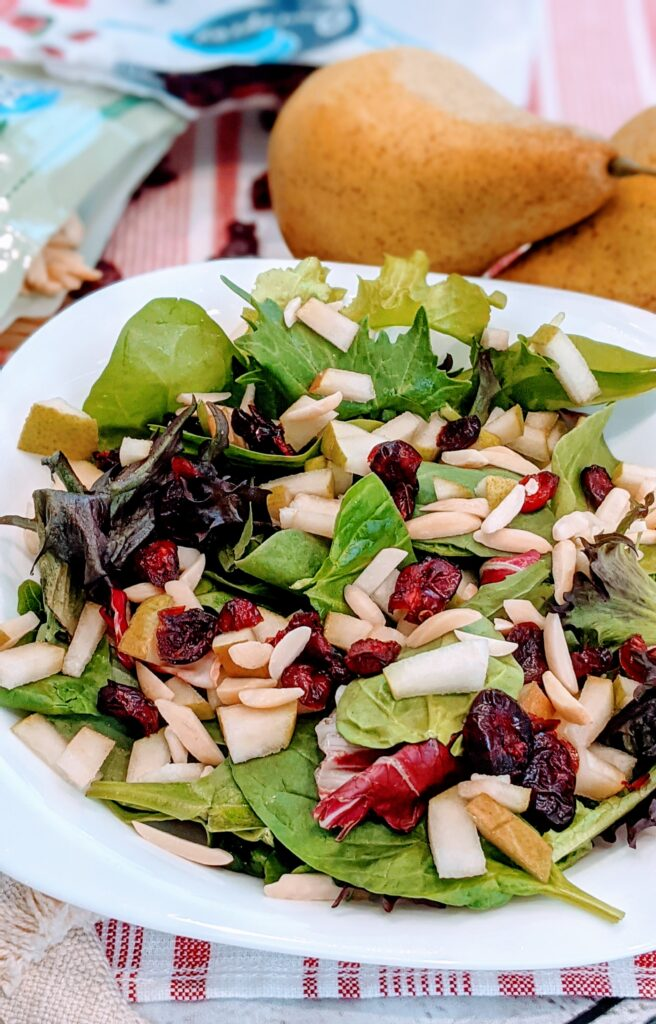CRANBERRY PEAR SUPER SALAD in white serving bowl alongside pears and other ingredients.
