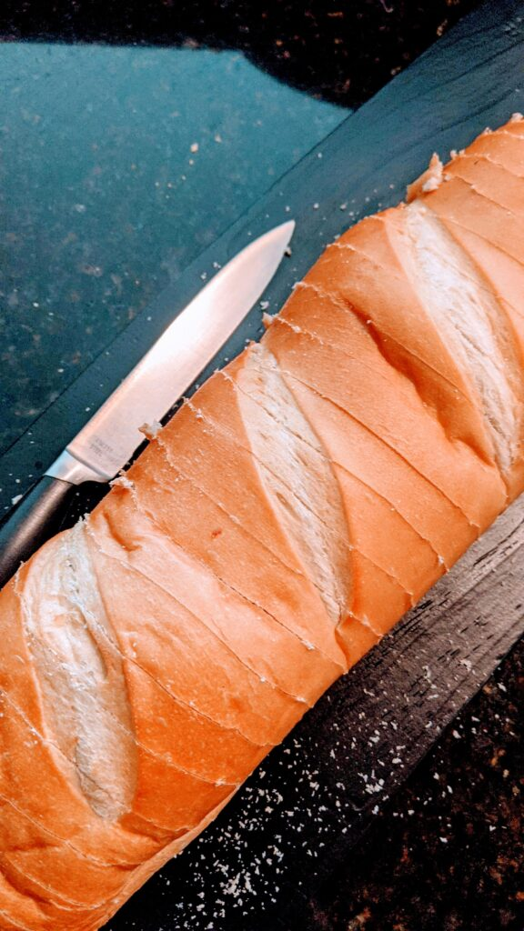 Bread sliced; half inch slices. with knife on side.