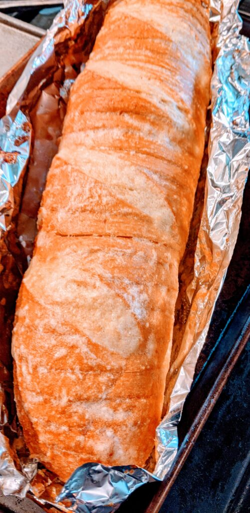 Garlic Parmesan French Loaf fresh from the oven, still remaining on the sheet of foil.