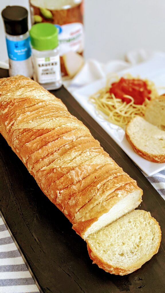 Garlic Parmesan French Loaf on black serving tray with surrounding ingredients.