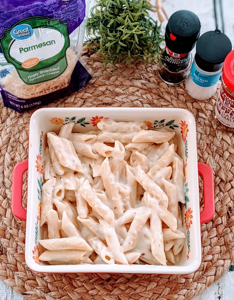 Low Fat Penne Alfredo in serving dish with surrounding ingredients.