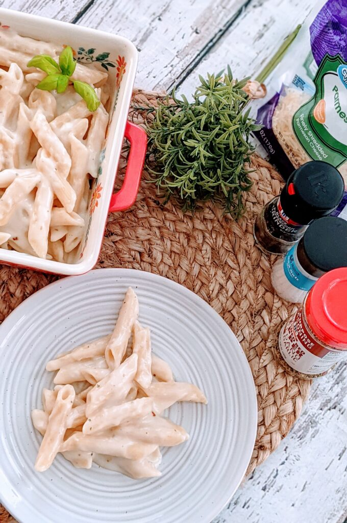 Low Fat Penne Alfredo on a plate and serving dish with surrounding ingredients.