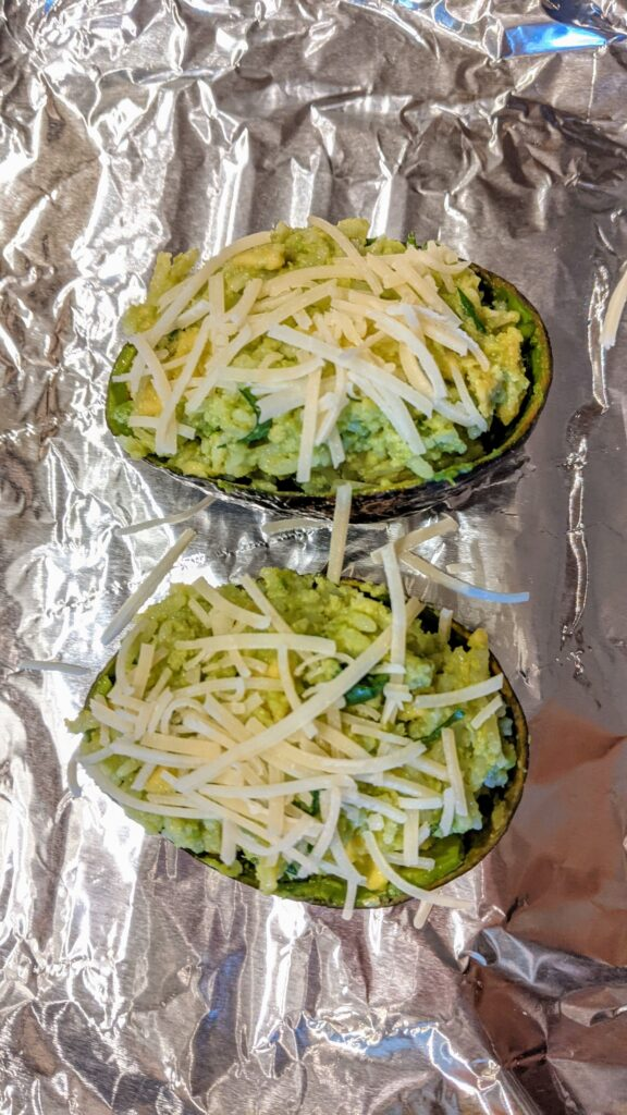 Filled avocado shells on foil covered baking sheet, ready to be placed in oven.