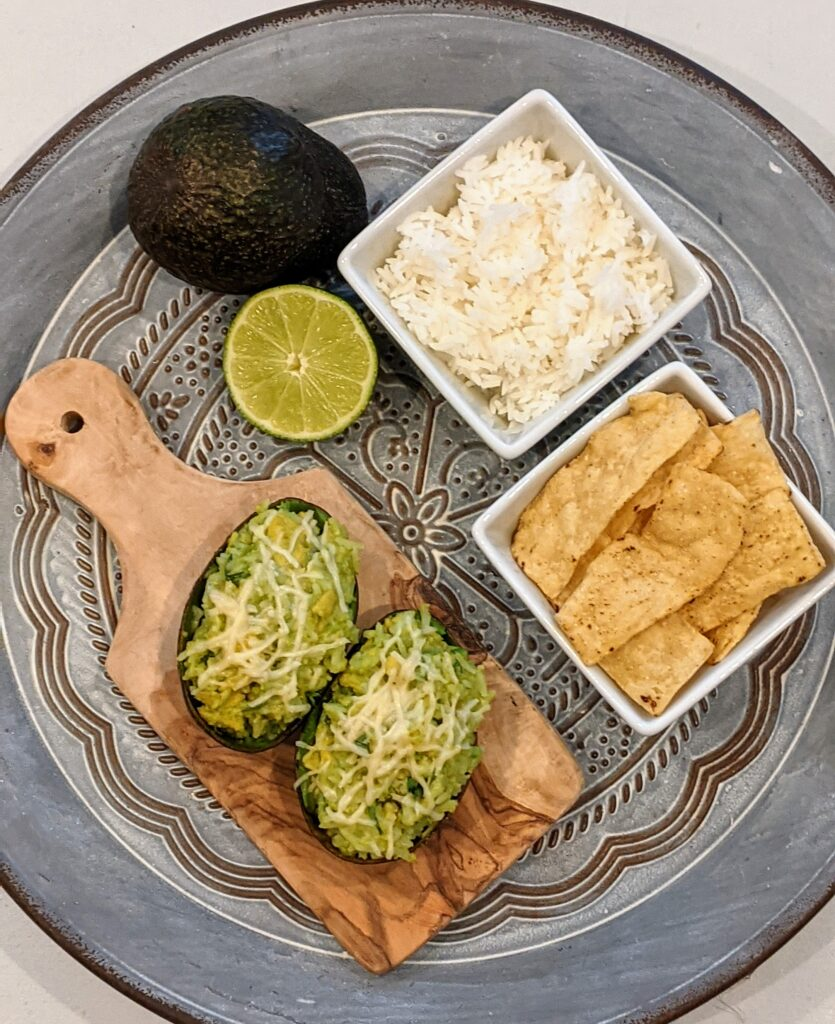 Broiled Avocado Parmesan Rice on serving tray with surrounding ingredients.