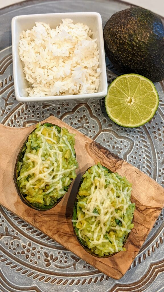 Broiled Avocado Parmesan Rice on small cutting board alongside ingredients.