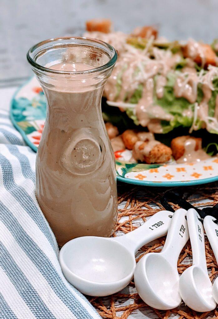 Easy Vegetarian Balsamic Caesar Dressing alongside a set of teaspoons and Caesar salad in background.