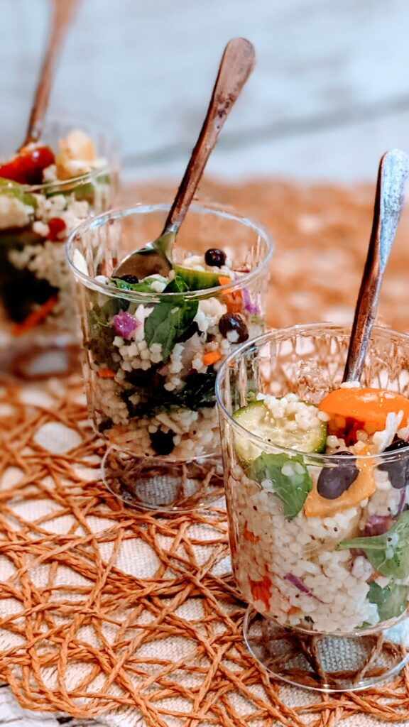 Salad in individual serving cups with spoons.