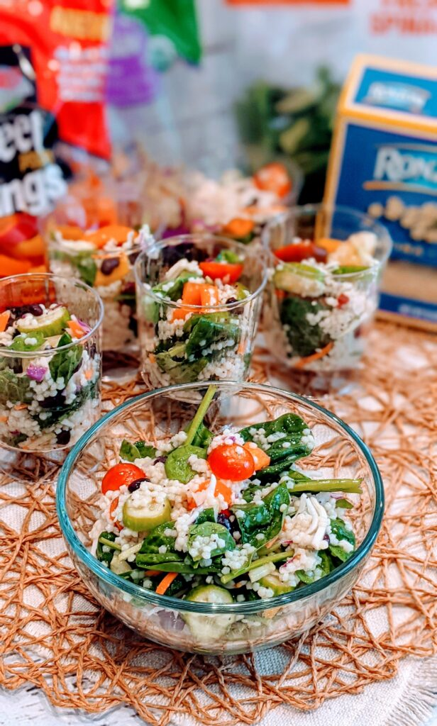 Simple Summer Salad in individual serving cups in addition to a individual bowl alongside ingredients.