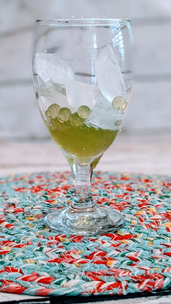 Bursting Boba and ice in glass on colorful placemat.
