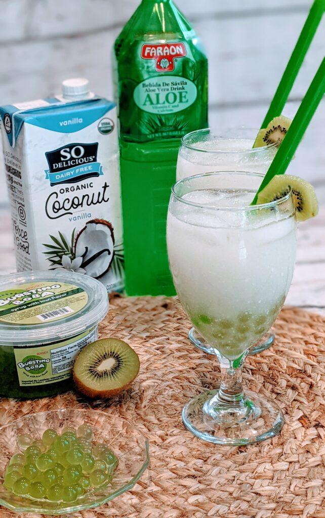 Drink garnished with kiwi.  Ingredients surrounding.